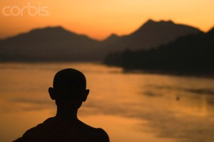 Buddhist Monk on the Mekong River at Sunset