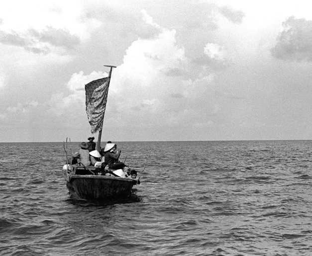 A 35 foot fishing boat approaches the amphibious command ship USS BLUE RIDGE (LCC 19). The BLUE RIDGE rescued 35 refugeees 350 miles northeast of Cam Ranh Bay, Vietnam, after they had spend eight days at sea in the boat.
